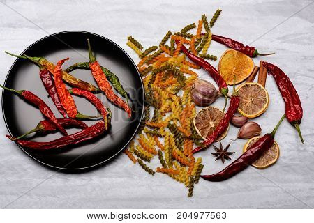 Red Pepper On Black Ceramic Plate With Pasta And Ingredients