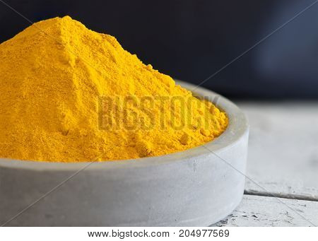 macro close up shot of powdered turmeric in a pile place in a light blue ceramic dish with a dark background copy space at header and side