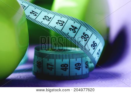 Measuring Tape And Green Dumbbells In Close Up