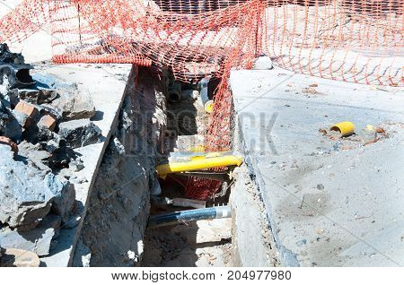 Open trench on the street excavation site with visible pipes for water gas and heating system
