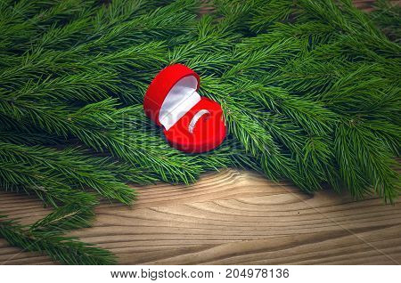 Wedding ring in heart shape box laying in Christmas tree branches on burnt wooden table background. Marriage Proposal. Christmas present gift.