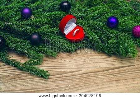 Wedding ring in heart shape box laying in Christmas tree branches with christmas balls around on burnt wooden board background. Marriage Proposal. Christmas present gift.