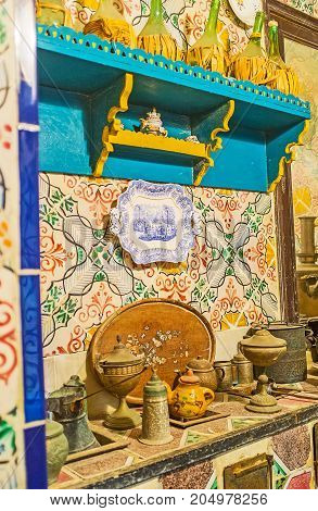 SOUSSE TUNISIA - SEPTEMBER 3 2015: The kitchen of Dar Essid mansion with vintage tableware wooden shelves and glazed tile on walls on September 3 in Sousse.