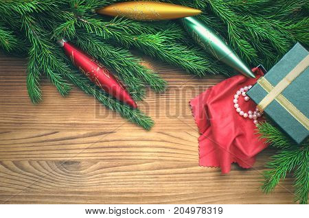 Christmas present box within pearl jewelry in fir tree branches with toy icicles around on burnt wooden board surface background with copy space. Christmas decorations.