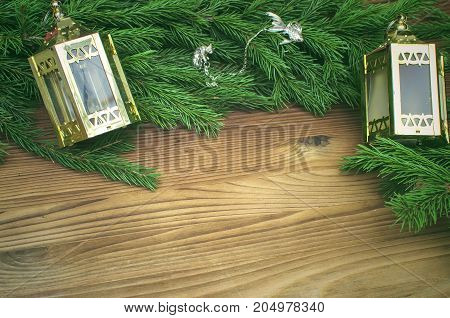 Silver jewelry present in fir tree branches with toy christmas lanterns around on burnt wooden board surface background with copy space. Christmas decorations.