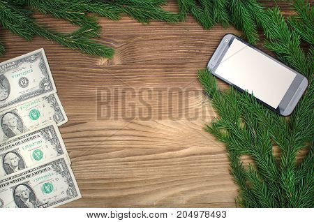 Mobile phone with isolated blank screen and money dollars laying in fir tree branches on burnt wooden board surface background with copy space. Christmas decorations.