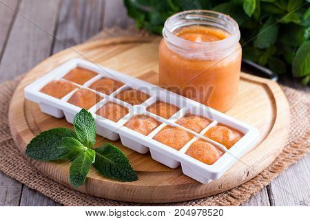 Fruit frozen cubes on a wooden table