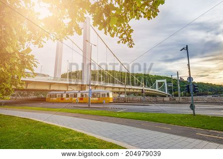 Budapest Hungary - Traditional yellow tram passing by under the Elisabeth Bridge at the Danube with Gellert Hill at background