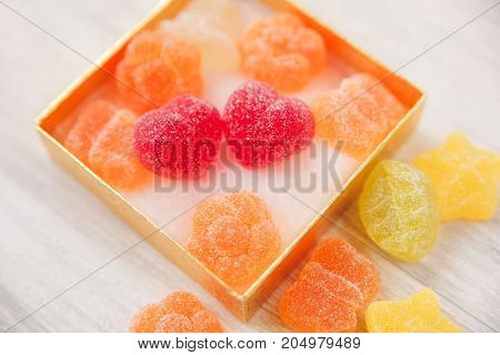 two heart shape jelly candy in golden present box.white wooden table.