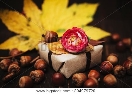 Gift box with flower and autumn decorations on the wooden background.Selective focus