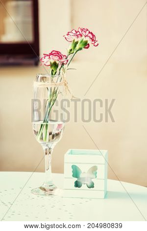 Cut geranium flower with decorative candle on the table in garden restaurant. Beauty photo filter.