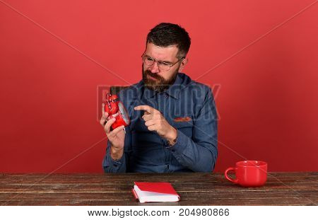 Man With Unsatisfied Face Sits At Wooden Desk
