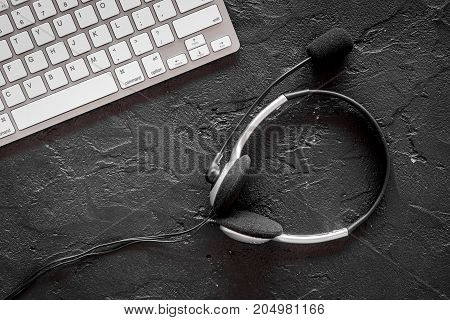 Call center manager's accessories. Headphones near keyboard on black background top view.