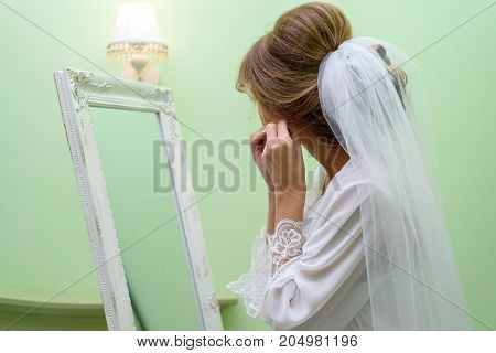 Beautiful Bride In Dressing Gown And Veil Putting Earring In Front Of Mirror Indoors, Side View. The
