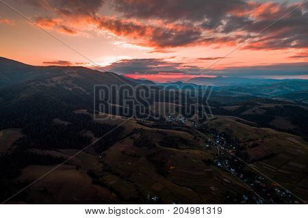 Beautiful nature landscape aerial view of the village in the Carpathian mountains against a beautiful sunset sky. The last rays of the sun make their way through the mountain range