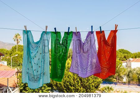 Four Colorful Bandanas Hanging On Rope Outdoor