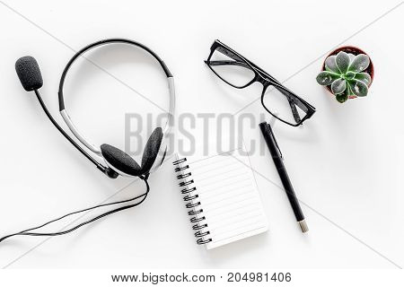 Call center manager's workplace. Headphones and notebook on white background top view.