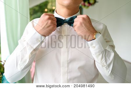 Close-up Of Businessman Or Groom Holding Bow-tie In Hands. Man Adjusting Or Correcting Emerald Bowti