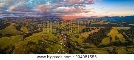 Beautiful nature landscape aerial view panorama of the village in the Carpathian mountains against a beautiful sunset sky
