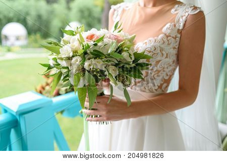 Beautiful wedding bouquet of fresh white and pink roses and greenery in bride hands outdoors free space. Bridal bouquet close up