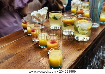 Glasses with colorful alcohol cocktails standing on wooden table