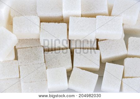 White sugar lumps. View from above. Abstract background