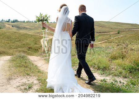 Happy bride and groom holding hands and walking in nature on wedding day. Wedding couple in love newlyweds free space. Bride in white dress with bridal bouquet and groom in black suit outdoors