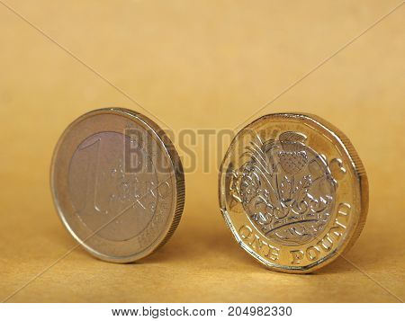 1 Pound And 1 Euro Coin Over Paper Background