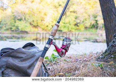 Fishing rod with spinning reel against the background of the lake