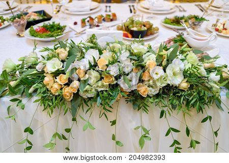 Lush floral arrangement of white and orange fresh flowers and greenery on wedding table for newlyweds. Beautiful flowers on table with white cloth free space. Luxury wedding table decorations