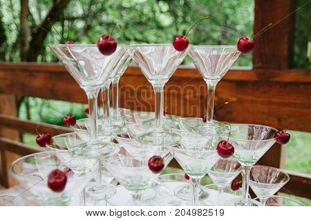Closeup of martini glasses arranged in the shape of a pyramid, standing on each other with red cherry inside