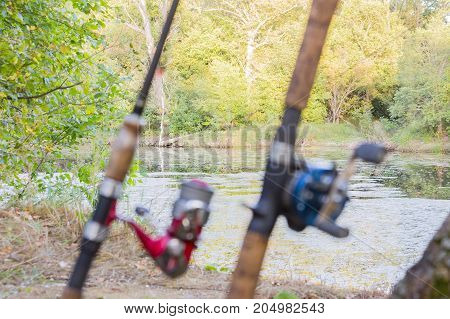 Blurred Front Background. Two fishing rods with reels. One reel spinning and second baitcasting reel