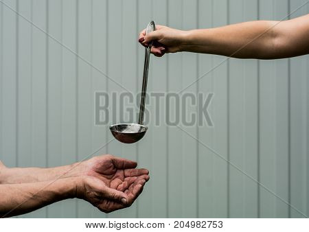 Female hand holding a ladle. The man folded his hands together forming a bowl.