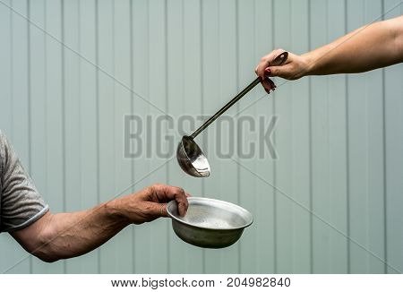 Female hand holding a ladle. A man holds a plate