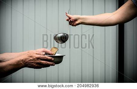 Female hand holding a ladle. The man in the hands holding a plate and a piece of bread.