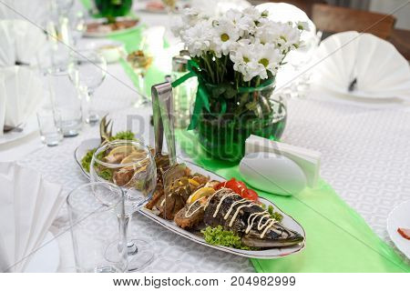 Stuffed sliced pike with salad on dinner table. Stuffed pike fish with lettuce leaves tomato and slices of lemon