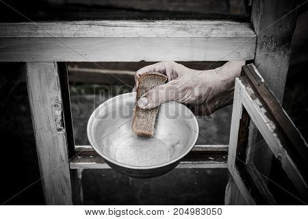 In his hand clamped aluminum plate and a piece of bread. The plate and the bread are passed through the window.