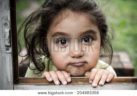Girl 3-4 years. She looks through the window.