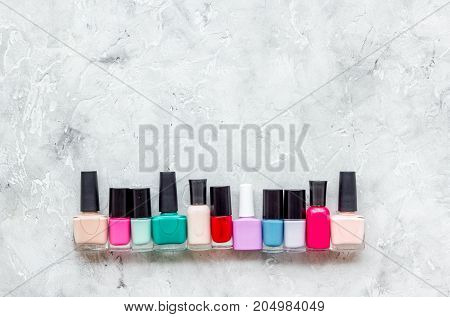 Choose nail polish for manicure. Bottles of colored polish on grey background top view