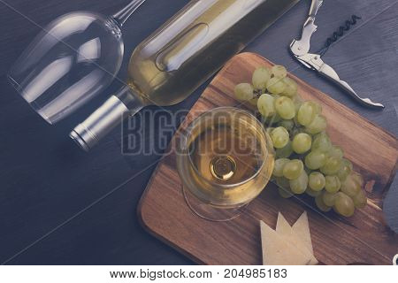 Bottle of white wine and wine glass with grape friut, retro toned