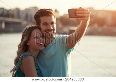 Photo of young happy couple taking selfie outdoor.