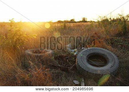 spontaneous dump discarded tires and household rubbish . garbage dump on the side of a dirt road. The problem of recycling garbage tires and environmental pollution by humans.