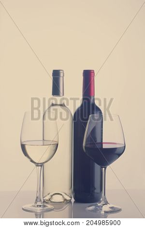 High glasses with red and white wine and two wine bottles, retro toned