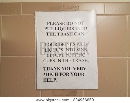 a paper sign in bathroom about not putting liquids in the trash can