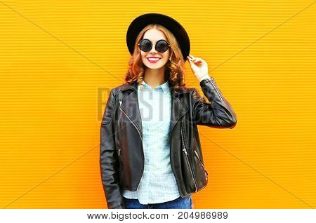 Fashion Smiling Woman In Black Rock Jacket, Hat Over Colorful Orange Background