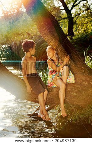 naughty boy and girl sitting on a branch over water, laughing, having fun talking