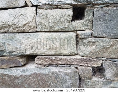 a grey stone wall with holes in it