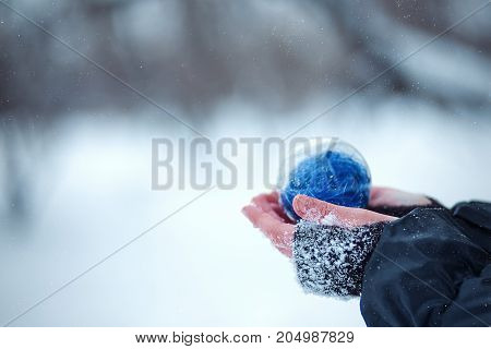 Christmas tree toy in the hands of a child. Round blue Christmas ball on snow background.