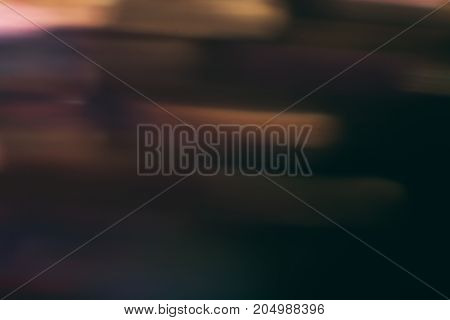 Abstract background of colorful blurs in motion on black. Bokeh of defocused streaks, blurred neon brown leds, glowing city lights and traffic, wallpapers and banners