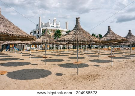 ALBANIA GOLEM- September 21 2015: Sandy beach on the Adriatic Sea umbrellas from the sun with thatched roofs.